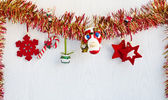Christmas decorations hanging from red and yellow tinsel. — Stock Photo