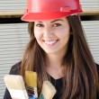 Stock Photo: Beautiful girl wearing red safety helmet.