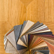 Different color samples of wood floor on brown parquet background. — Stock Photo
