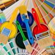 Paint cans and brushes on stripes of color sample. — Stock Photo