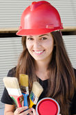 Beautiful girl wearing a red safety helmet. — Stock Photo
