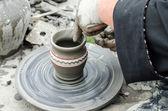 从车轮上的粘土制作陶器的手的特写镜头. — 图库照片