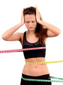 Measuring bust, waist, hips. Unhappy fit girl wrapped with three measuring tapes in inch. — Stock Photo