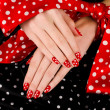 Stock Photo: Close up on beautiful female hands with cute red manicure with white dots.