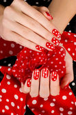Close up on beautiful female hands with cute red manicure with white dots. — Stock Photo
