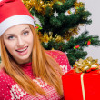Beautiful young woman with Santa hat smiling holding a big Christmas present. — Foto de Stock