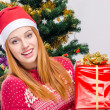 Beautiful young woman with Santa hat smiling holding a big Christmas present. — Stok fotoğraf