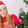 Beautiful young woman with Santa hat decorating the Christmas tree. — Stok fotoğraf