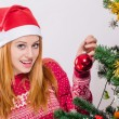 Beautiful young woman with Santa hat decorating the Christmas tree. — 图库照片