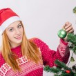 Beautiful young woman with Santa hat decorating the Christmas tree. — Stock Photo #34950407