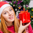 Beautiful young woman with Santa hat smiling holding a Christmas present. — Stockfoto