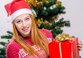 Beautiful young woman with Santa hat smiling holding a big Christmas present. — Stock Photo