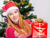 Beautiful young woman with Santa hat smiling holding a big Christmas present. — Stockfoto