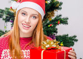 Beautiful young woman with Santa hat smiling holding a big Christmas present. — Photo