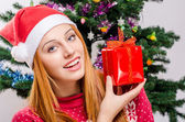 Beautiful young woman with Santa hat smiling holding a Christmas present. — Foto Stock