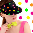 Portrait of a young woman wearing a colorful polka dotted hat and a neon green bowtie.  — Stock fotografie
