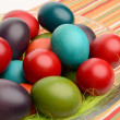 Colorful hand dyed easter eggs in a bowl on a table with striped tablecloth. — Foto de Stock