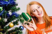 Beautiful young woman smiling holding a Christmas present. — Stock Photo