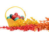 Colorful hand dyed easter eggs in a yellow basket. — Stock Photo