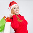 Happy young woman with Santa hat shopping for the Christmas holidays. — Stock Photo