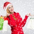Happy young woman with Santa hat shopping for the Christmas holidays, snowy background. — Stock Photo #35762089