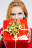 Beautiful young woman holding in front a big Christmas present. — Foto Stock