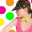 Girl wearing a colorful polka dotted visor and a neon green bowtie. — Stock Photo