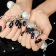 Stock Photo: Close up on beautiful female hand with black manicure.