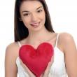 Beautiful brunette girl holding a red heart. Happy woman, Valentine day. Focus on the heart, blur on the model. — Stock Photo #38891555