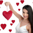 Beautiful brunette girl holding up a red heart. Happy woman, Valentine day. Hearts background. — Stock Photo