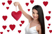 Beautiful brunette girl holding up a red heart. Happy woman, Valentine day. Hearts background. — ストック写真