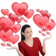 Beautiful brunette girl raising her hand presenting. Valentine day. Many red hearts background. — Stock Photo