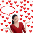 Beautiful brunette girl raising her hand presenting. Valentine day. Many red hearts background and blank bubble speech. — Stock Photo #39260179