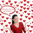Will you be my Valentine? Beautiful brunette girl asking the Valentine question. Valentine day. Many red hearts background and bubble speech. — Stock Photo