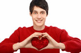 Handsome man holding up a red heart. Valentine day. — Stock Photo