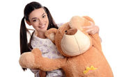 Beautiful woman with a big teddy bear.Happy brunette girl playing with a big teddy bear. — Stock Photo