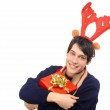 Handsome young man dressed for Christmas, wearing reindeer horns. Man holding a gift smiling. — Stock Photo