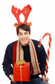 Handsome young man dressed for Christmas, wearing reindeer horns. Man holding a gift and a big candy cane smiling. — Stock Photo