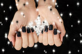 Close up on beautiful female hand with black manicure. — Stock Photo