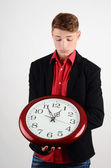 Business time. Business man holding and looking to a big clock. — Foto de Stock