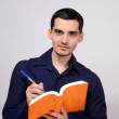 Student holding a book smiling. Teacher writing on a notebook. — Foto Stock