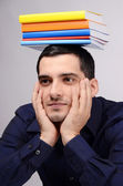 Student holding a pile of books on his head. Funny teacher with colorful books over his head. — Stockfoto