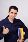 Estudiante feliz sosteniendo una pila de libros bajo el brazo firmando los pulgares para arriba. profesor con coloridos libros en su mano sonriendo. — Foto de Stock