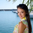 Tropical summer vacation. Beautiful girl smiling standing under a palm tree. — Stock Photo