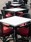 Rows of white empty tables and black wicker chairs in an open air cafeteria. — Stock Photo