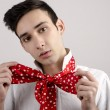Young attractive stylish man in white shirt tying a red scarf with dots around his neck. — Stock Photo