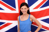 Portrait of a beautiful British girl smiling. Young woman standing with the UK flag in the background. — Stock Photo
