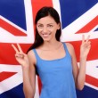 Portrait of a beautiful British girl smiling and signing victory. — Stock Photo
