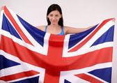 Beautiful British girl smiling holding up the UK flag. — Stock Photo