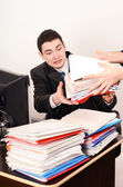 Desperate business man receiving a lot of paper work. — Stock Photo